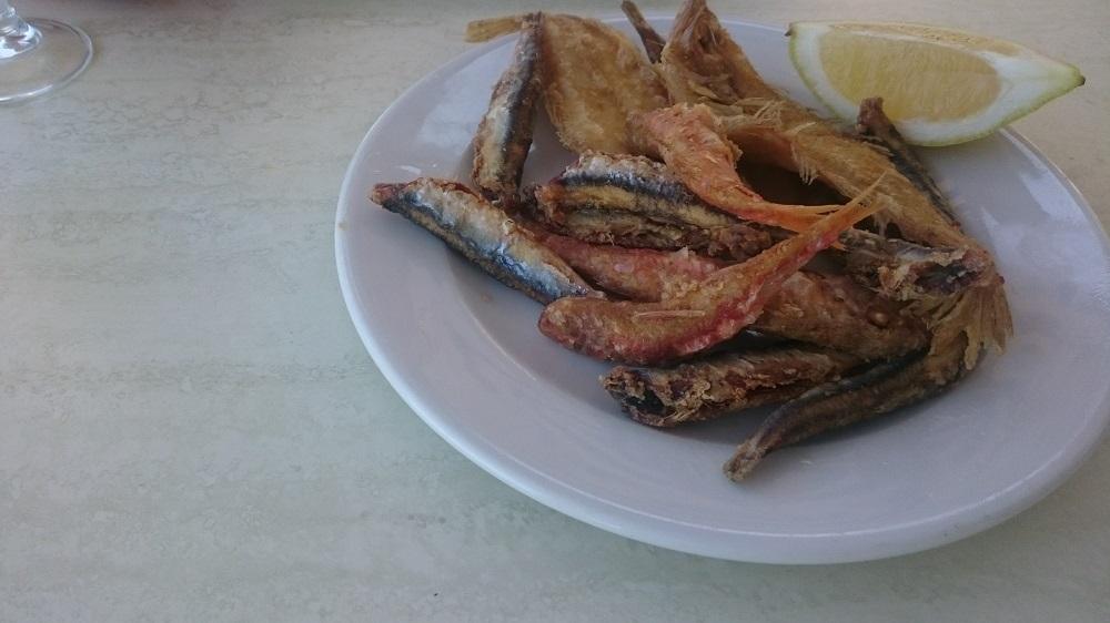 Gefrituurde visjes aan het strand eten.