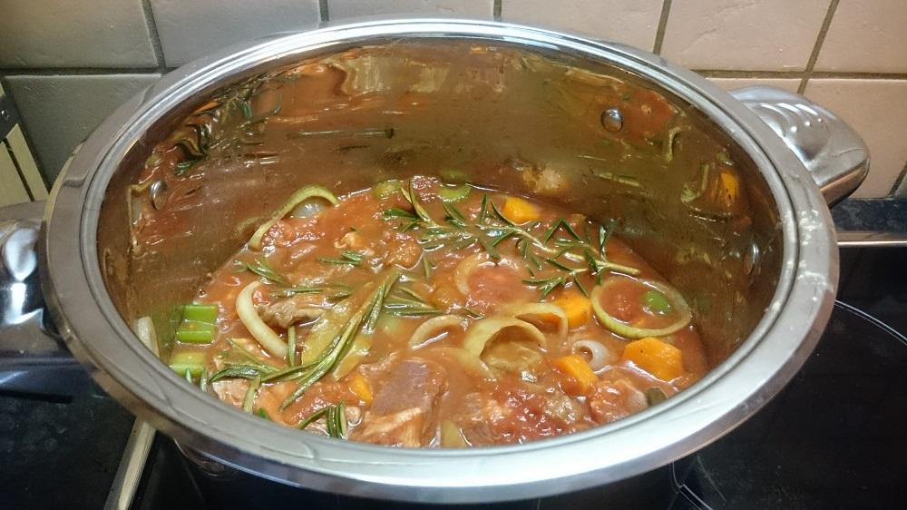 Stoofpotje in de maak met ui, rozemarijn, wortel, selderij, tomaat, bouillon en witte wijn