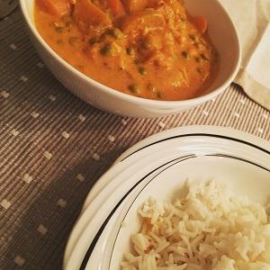 Curry met zalm in kokos-bouillon, met zoete aardappel, wortel en erwten